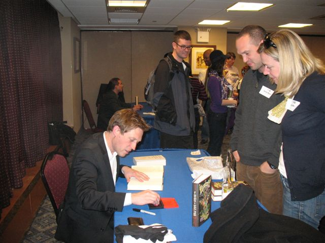 James Kennedy re-reads his novel while onlookers wait for an autograph
