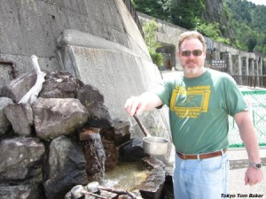 Tom Baker samples water from a spring above Kurobe Dam in Toyama Prefecture.